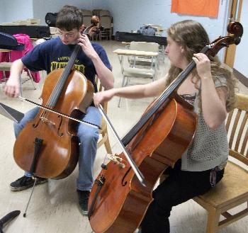 Student teaching another student cello